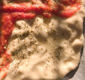 Making a pizza. A detail of a raw pizza pasta with tomato topping, low angle light Stock Photos