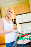 Making Pizza. A young attractive woman in the kitchen making pizza stock photography