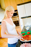 Making Pizza. A young attractive woman in the kitchen making pizza royalty free stock photography