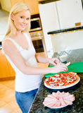 Making Pizza. A young attractive woman in the kitchen making pizza stock images