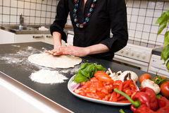 Making Pizza Dough. A female making pizza dough at home in the kitchen on the counter royalty free stock photo