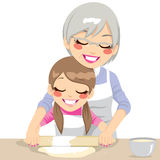 Making Pizza Dough Together. Granddaughter and Grandmother making handmade pizza dough using rolling pin Stock Image