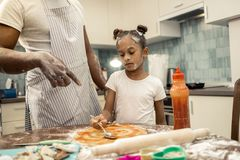 Father wearing striped apron teaching his little girl making pizza stock photography