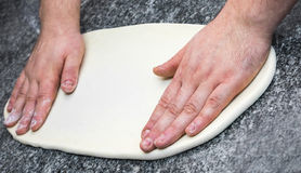 Making the Pizza - Hands Detail. Detail of hands making the pizza on a table Stock Image