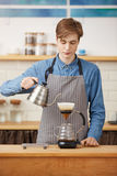 Making pourover coffee. Nice barista preparing coffee drink, looking concentrated. Royalty Free Stock Photos