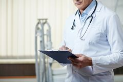 Making prescriptions. Doctor in uniform making notes in medical document after visit of patient Stock Photography