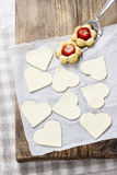 Making puff pastry cookies in heart shape filled with strawberri Stock Image