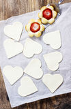Making puff pastry cookies in heart shape filled with strawberri Stock Photos