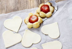 Making puff pastry cookies in heart shape filled with strawberri Stock Photography