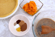 Making pumpkin pie - pastry crust, pumpkin, spices and filling Stock Photos