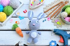 Making rabbit with carrot. Crochet bunny for child. On table threads, needles, hook, cotton yarn. Handmade crafts. DIY concept. Sm. All business. Income from stock photography