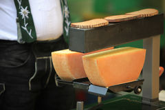 Making raclette cheese on a farmer's market. Brown bread and melted Raclette cheese on a Swiss farmer's market Royalty Free Stock Images