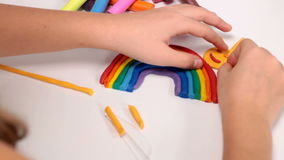 Making a rainbow from plasticine. Little girl completing an art project stock video footage
