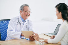 Making recomendations. Vietnamese mature doctor with tablet computer talking to patient stock photography