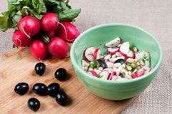 Making red radishes and olives salad Royalty Free Stock Photo