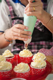 Making red velvet cupcakes. The action of making red velvet cupcakes. Woman hand piping cream cheese on cupcake Stock Photography