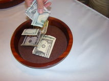 Making a Religious service money offering. Single hand placing money in a woooden Church service collection plate royalty free stock photography