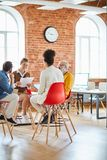 Making report. Four adults in casualwear discussing data at briefing while sitting on chairs in front of each other stock image