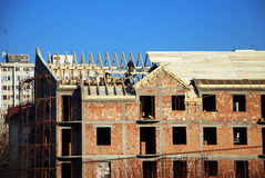 Making a roof. Brick building with wooden roof and workers over blue sky Royalty Free Stock Photos