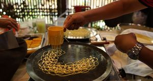 Making roti jala or net bread. A man showing how to make roti jala.Roti Jala, literally meaning & x22;Net Bread& x22;, is a popular Malay tea time snack served stock photo