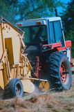 Making round hay. Tractor pulling hay bailer for round bales royalty free stock photography