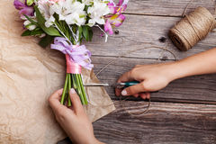 Making a rustic bouquet from gillyflowers and alstroemeria on ol Stock Image