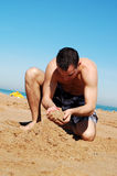 Making sandcastle. Young guy enjoying the sun on the beach and making a sandcastle Royalty Free Stock Photography