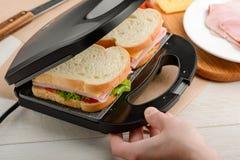 Making sandwiches using panini press. Making sandwiches using a panini press. Snacks with toast bread, cheese, veggies and ham stock image