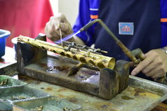 Making saxophone. A technician is welding some component parts of saxophone Stock Photography