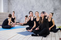 Making selfie. Group of girls in fitness class at the break looking at cell phone, happy and smiling, show funny face Stock Photos