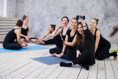 Making selfie. Group of girls in fitness class at the break looking at cell phone, happy and smiling, show funny face Stock Photo