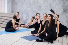 Making selfie. Group of girls in fitness class at the break looking at cell phone, happy and smiling, show funny face stock images