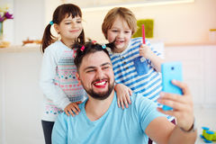 Making selfie snap shot with crazy hairstyle and makeup when you home alone with children. Making funny selfie snap shot with crazy hairstyle and makeup when you royalty free stock photo