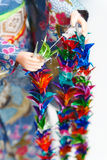 Making Senbazuru (a thousand origami cranes). A Japanese doll in Kimono arranging parts of a Senbazuru. Shallow depth of field stock images
