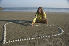 Making shell heart. Young girl making heart from shells on the sand Stock Image