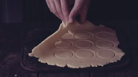 Making shortbread cookies by woman's hands over old wooden table with blue stamp with inscription Home Made. Dark rustic style stock video footage