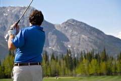 Making the Shot. A golfer tees off on a mountan golf course royalty free stock photos