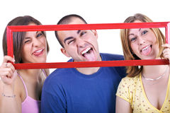 Making silly faces. Three young students holding frame and making silly faces Stock Image