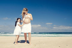 Making a smile on mom's belly. Beautiful pregnant women in the beach with her little daugther making a smile on mom's belly with sunscreen Stock Images