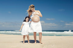 Making a smile on mom's belly. Beautiful pregnant women in the beach with her little daugther making a smile on mom's belly with sunscreen Stock Photography