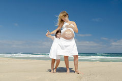 Making a smile on mom's belly. Beautiful pregnant women in the beach with her little daugther making a smile on mom's belly with sunscreen Royalty Free Stock Image