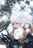 Making a snowball. Beautiful young woman enjoying making a snowball Royalty Free Stock Photo