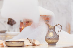 Making soap foam for massage. Water jar, towel and copper bowl w Stock Photo