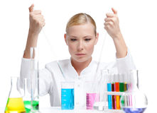 Making some experiments. Chemical female researcher surrounded with vials and flasks makes some experiments, isolated on white Stock Photography