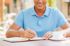 Making some important notes. Close-up of confident mature man writing something in his note pad and smiling while sitting at the table outdoors with house in Royalty Free Stock Images