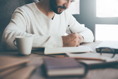 Making some important notes. Close-up of confident young man writing something in notebook while sitting at his working place in office Stock Photo