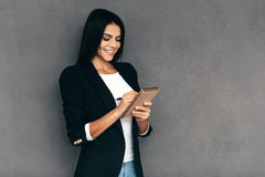 Making some notes. Attractive young woman in smart casual wear writing something in her notebook and smiling while standing against grey background Royalty Free Stock Image
