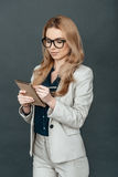 Making some notes. Attractive young woman in smart casual wear writing something in her notebook and smiling while standing against grey background Royalty Free Stock Photo