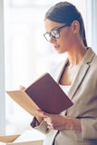 Making some notes. Close-up of pensive young beautiful businesswoman in glasses writing in notebook while standing in front of window Royalty Free Stock Photo