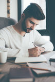 Making some notes. Confident young man writing something in notebook while sitting at his working place in office Royalty Free Stock Images
